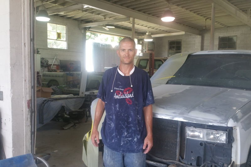 andy standing in front of truck at shop